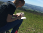 Student sitting in grassy field writing in notebook
