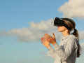a woman wears VR goggles standing in front of sky and clouds