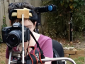 woman looking into a camera using assistive technology on wheelchair